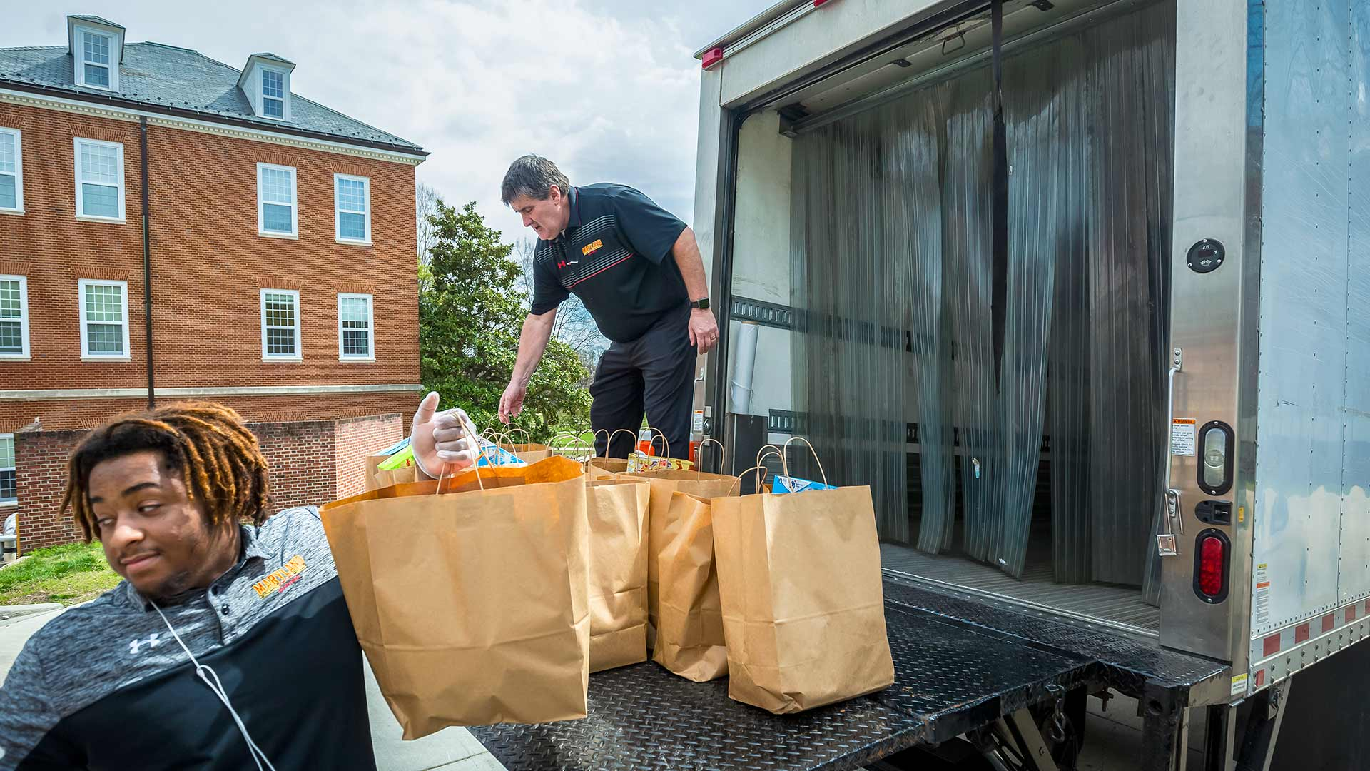 Dining Services employees Michael Norman (left) and Larry Tumlin unload preassembled bags of food at the Campus Pantry in March 2020, when the facility's clientele tripled in the wake of the pandemic and widespread shutdowns. A new contribution of more than $400,000 from the Student Government Association includes about $300,000 to support the Campus Pantry. (Photo by Stephanie S. Cordle)