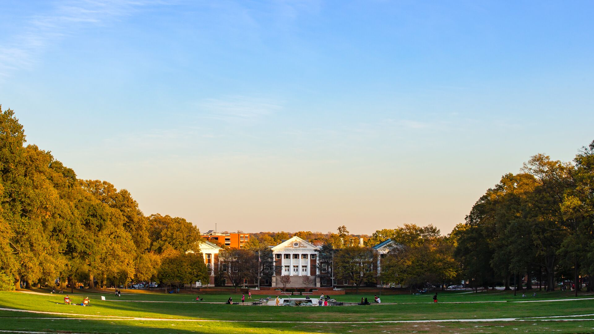 View of the Mall at dusk looking towards Miller Administration Building with students in masks.