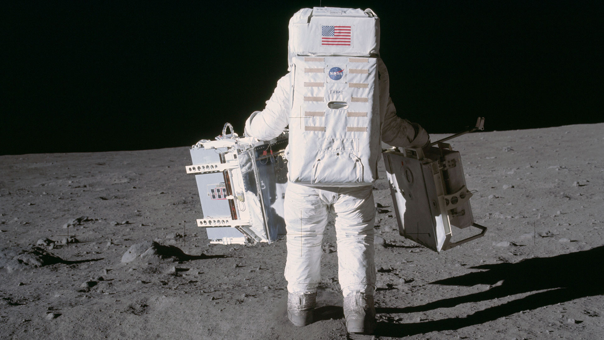 Astronaut Buzz Aldrin carries two pieces of science equipment during the Apollo 11 extravehicular activity in July 1969. In his right hand is a mirror array designed by UMD physicists Doug Currie and the late Carroll Alley, along with a national team. (Photo by Neil Armstrong/NASA)